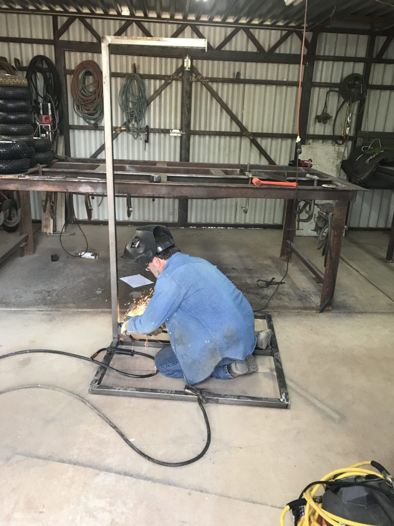 neighbor welding together a hammock chair stand for my sons therapy swing